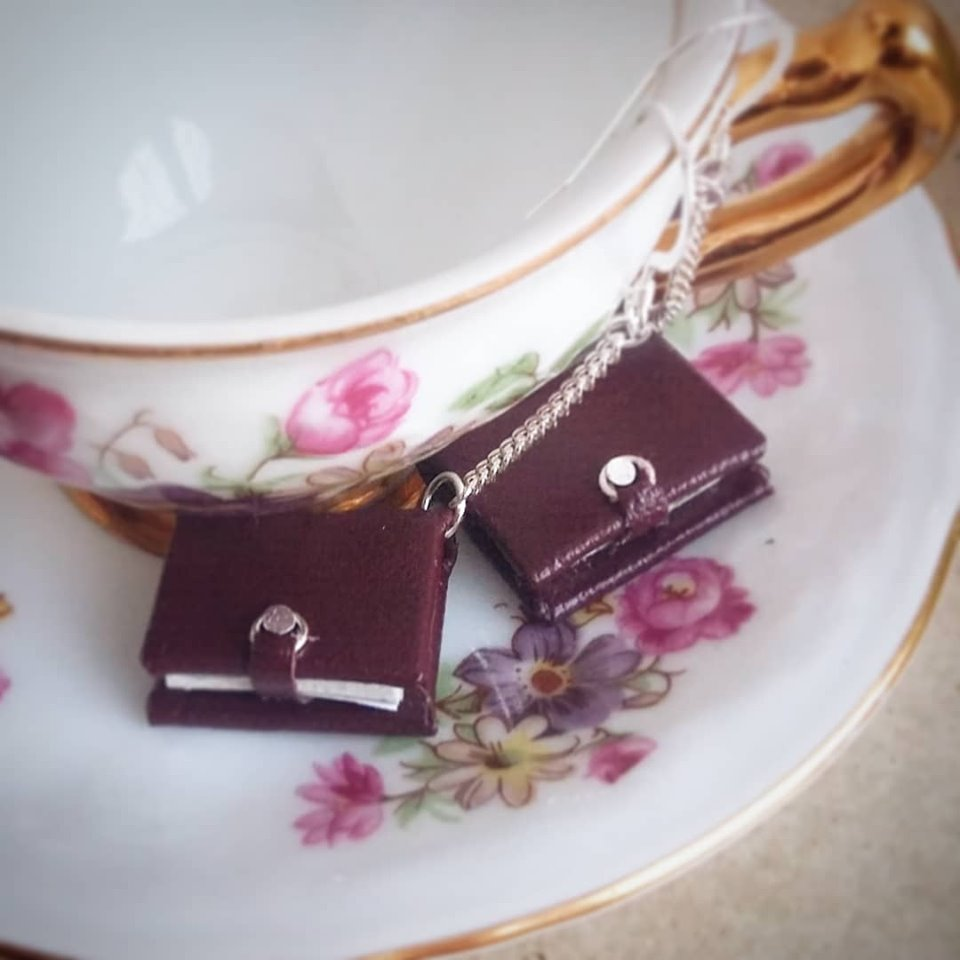 miniature book earrings resting on a teacup