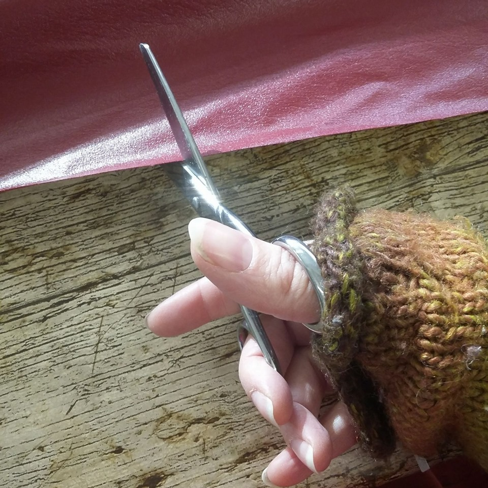 A hand wearing fingerless gloves cutting bookcloth